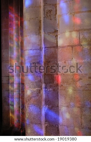 Stained glass windows throwing coloured light onto columns in Ely Cathedral