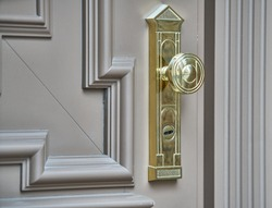 stainless door knob or handle on wooden door in beautiful lighting.
