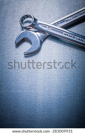 Stainless flat spanner and hook wrench on metallic background construction concept