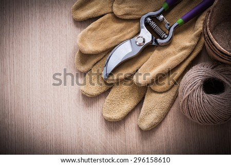 Stainless garden pruner leather safety gloves peat pots and hank of rope on vintage wooden board gardening concept.
