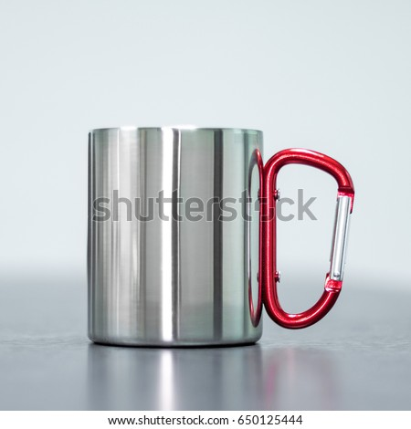 Stainless mug on table. Tin cup and handle clip for your design. #650125444
