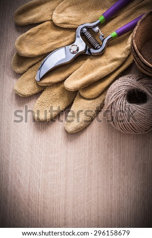 Stainless secateurs leather safety gloves peat pots and hank of string on vintage wooden board gardening concept.