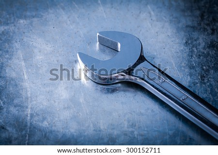 Stainless spanner wrench on scratched metallic background close up view construction concept.