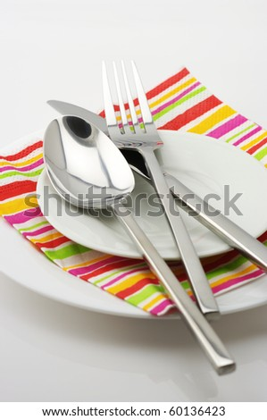 Stainless spoon, fork and knife on white plates with multicolored striped paper napkin.