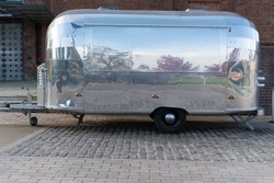 Stainless steel airstream caravan with reflection outside the Royal Shakespeare Theatre in the UK