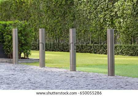 stainless steel bollards on floor between road and green grass