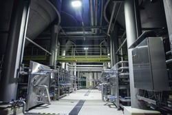 Stainless steel brewing equipment : large reservoirs or tanks and pipes in modern beer factory. Brewery production concept, industrial background