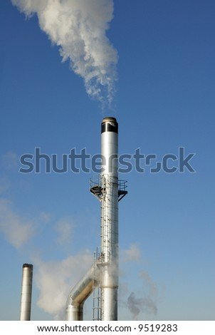 Stainless steel chimney stack with smoke coming out of the top.