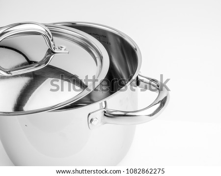 Stainless steel cooking pot with matal lid and handles isolated on white background.