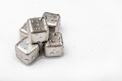 Stainless steel cubes simulating ice for cooling drinks with dew on white background