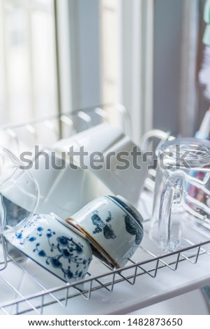 Stainless steel drain dish rack with utensils on the sink under the kitchen window sill
