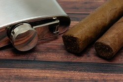 Stainless Steel Flask and Cuban cigars on a table.