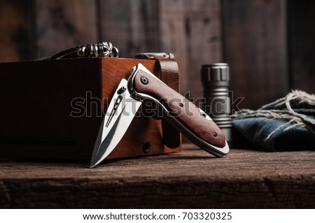 stainless steel folding knife with wooden handle and other everyday carry (EDC) items for men. closeup at folding knife.