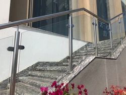 stainless steel Glass or glazed hand rail at entrance stair case steps with the planter box flowers which giving elegant look reception area of an  commercial building
