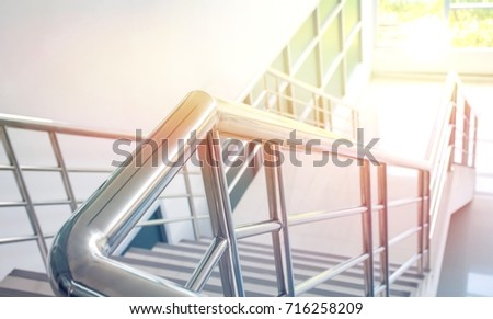 Stainless steel handrail and white stair in office building with lighting effect