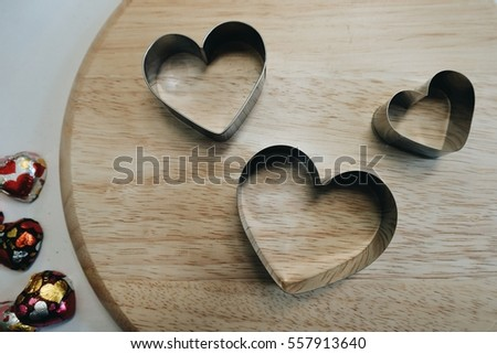 Stainless steel heart shape for making cookies or pancakes and more,Making sweets for Valentine's Day,And dessert in many sizes on wooden background. #557913640