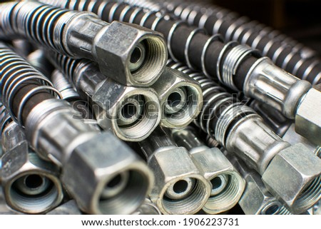 Stainless steel hydraulic hoses close up. Brake hoses car, truck, tractor, heavy machinery. Industrial background.