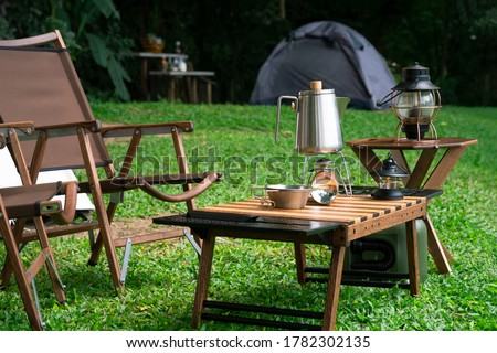 Stainless steel kettle, portable gas stove, bowl and vintage lanterns with outdoors table set on green lawn in camping area