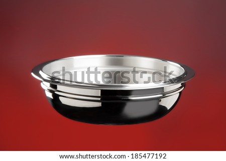 Stainless steel kitchen bowl on red background
