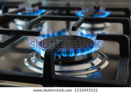 Stainless steel kitchen surface with cast-iron grill. Burning gas burners. Сток-фото ©