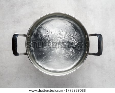 Photo of  Stainless steel metal cooking pot of boiling water on gray concrete background , top view.