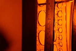 Stainless steel metal ruler and plastic circle mall ruler hanging on with paper on dark brown wood with yellow lights