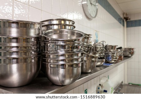 Stainless steel mixing bowls on a stainless steel shelf in an industrial kitchen