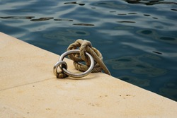 Stainless steel mooring ring with ropes tied on it on a wharf with water in background. Long exposure shot.