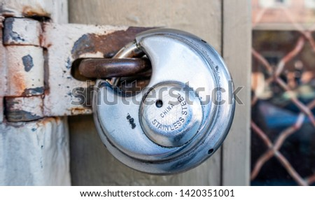 Stainless steel padlock with weathering and scratch marks in the locked position. Signifies privacy and safety of the property owner. #1420351001