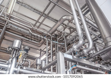 Stainless steel pipes in the factory. Construction on food production, Abstract industry background. Modern successful production. Job search, employment in the enterprise. Manufacturing business