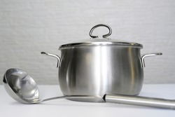 Stainless steel pot, stockpot and a ladle on white table, eco friendly kitchen utensils without harm, harmless safe for people