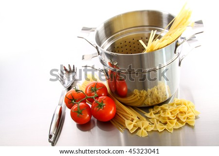 Stainless steel pot with uncooked pasta and tomatoes