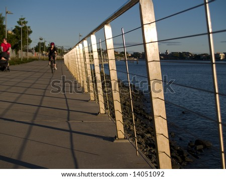 Stainless steel railing along boardwalk of river with pedestrians in distance