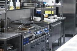 Stainless steel restaurant professional kitchen equipment and work surface. The indoor kitchen. None of the people. The light was on