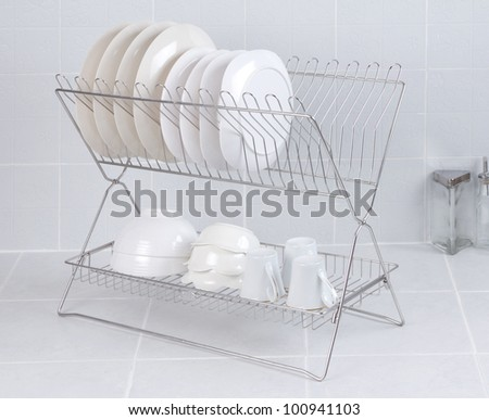Stainless steel shelf for keeping dishes and cups on gray tile background