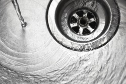 Stainless steel sink plug hole close up with water