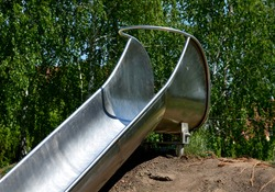 stainless steel slide on a playground with grassy hills. playground with stone walkways made of natural sandstone stone. a pipeline tunnel runs through the hill