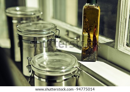 Stainless steel storage containers and bottle of olive oil in kitchen on windowsill shelf in warm sunlight.