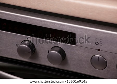 stainless steel stove with knobs in a modern kitchen