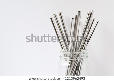 Stainless steel straws in glass jar with white copy space.