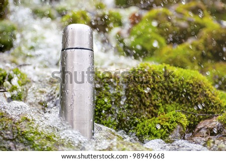Stainless steel thermos is in the turbulent river water - stock photo