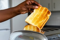 stainless steel toaster toaster with toasted bread for breakfast inside with kitchen in the background. Hands of African American Female pulls out ready toasts.
