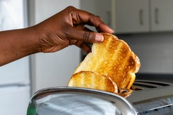stainless steel toaster toaster with toasted bread for breakfast inside with kitchen in the background. Hands of Black African Woman pulls out ready toasts.