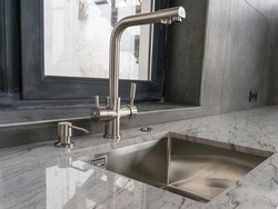 Stainless steel undermount kitchen sink and faucet with light marble countertop