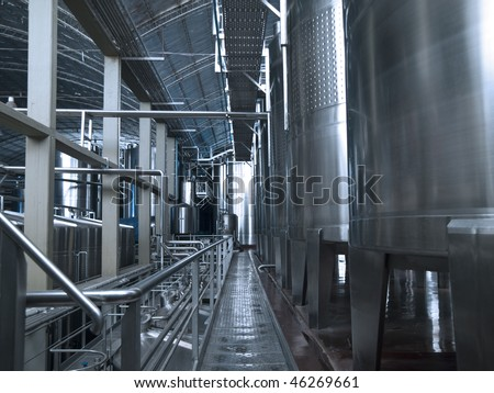 Stainless steel wine vats in a row inside the winery.