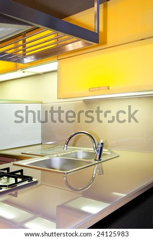 Stainless still sink and faucet in yellow kitchen