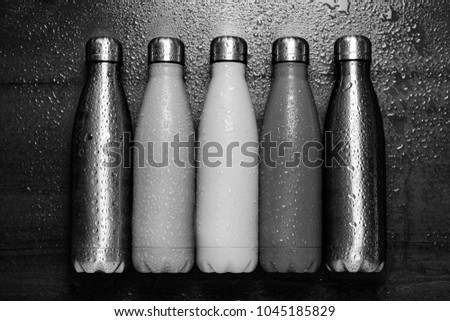 Stainless thermos bottles on a wooden table sprayed with water. Black and white.