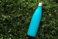 Stainless thermos water bottle isolated on green grass outdoor. Light blue matte color. Horizontal photo without effects.
