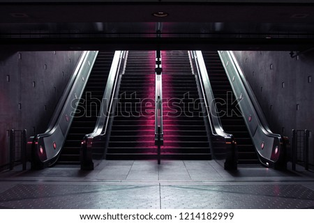 Staircase and Escalators leading down into a Subway Station with Neon Lights