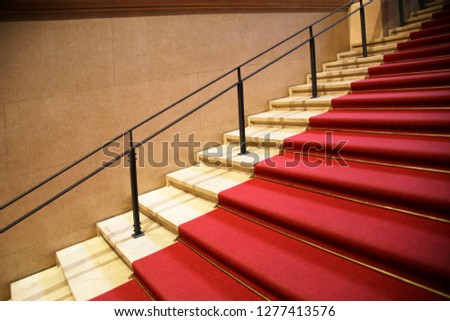 Staircase covered by red carpet runner. Solemn / ceremonial architecture fragment in a concept of success or celebration or festival. stock photo